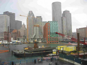 Cranes lift girders onto buildings under construction in Boston's waterfront